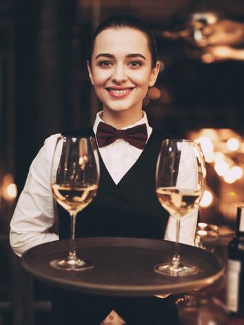 joyful-waitress-holding-tray-with-glasse