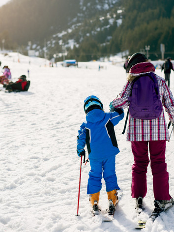 rear-view-of-little-skiers-first-steps-t