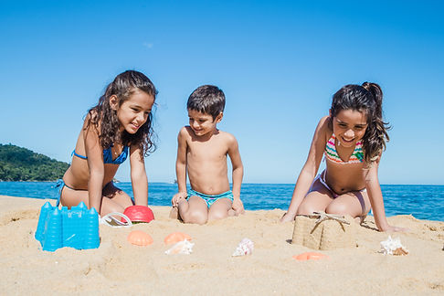 boy-playing-with-his-sisters-on-the-sand