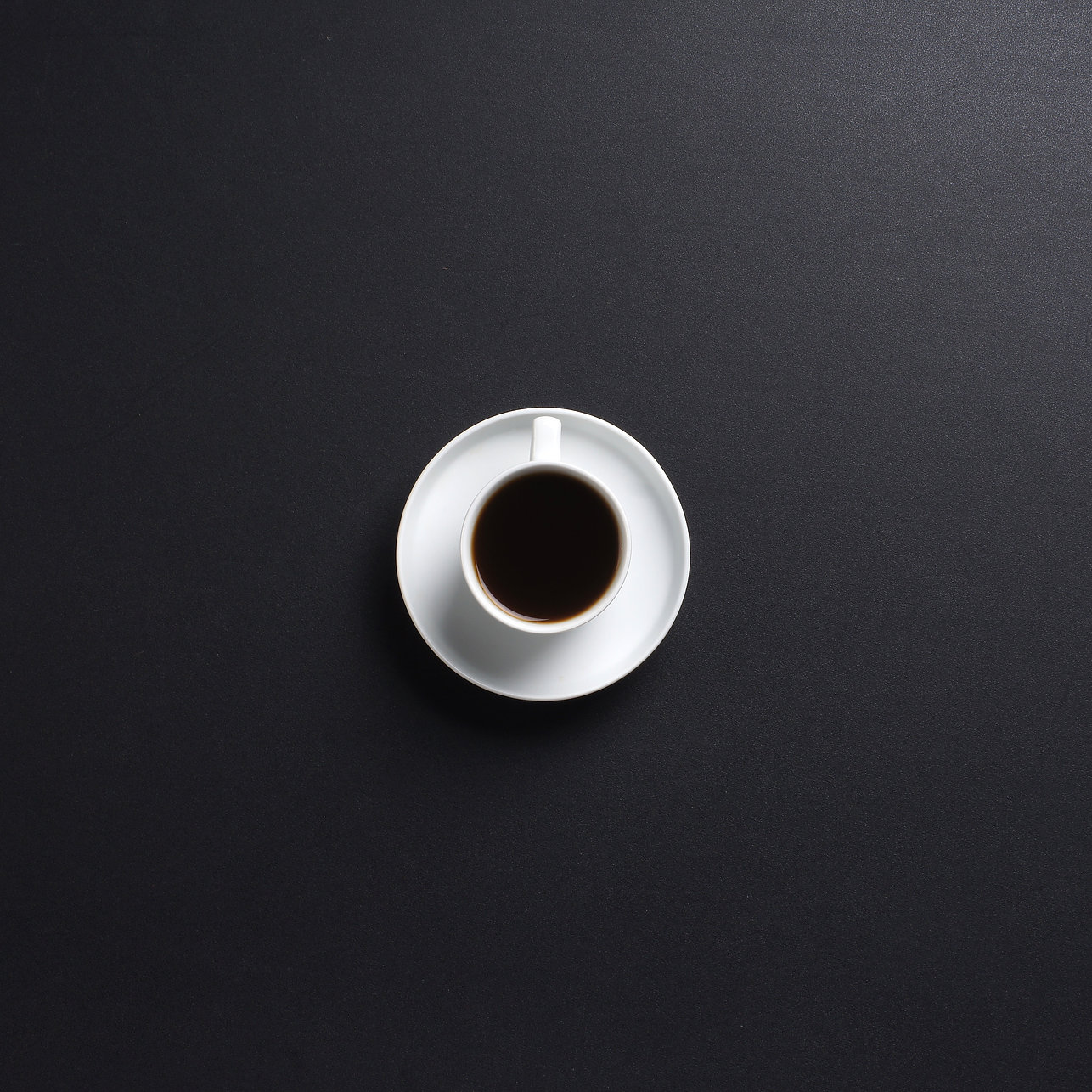 Cup of coffee over the black background.