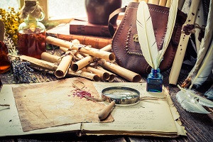 Cluttered desk full of scrolls, herbs, writings, and quills. A window in the background provides light. Image by iStockphoto/Shaiith