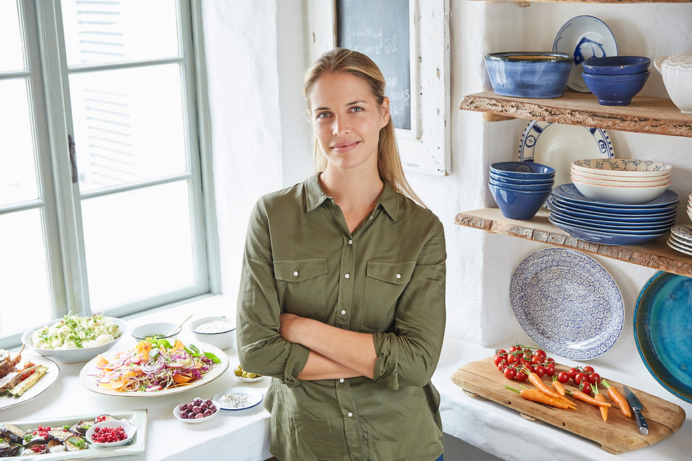 nutritionist standing next to a table with healthy food