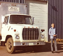 Founder, A.M. Dockery, standing beside a Dockery Floor Clovering Truck