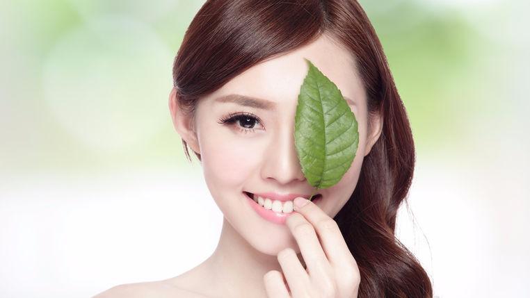 Mujer con hoja de té verde