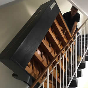 A member of our professional transport team moving a piano up a flight of stairs.