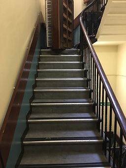 Piano removal in London on a flight of stairs