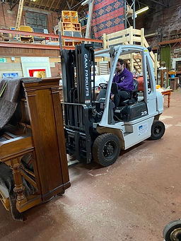 Moving an upright piano in a studio in Sheffield using a forklift