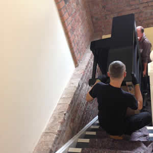 Our expert piano removal team lifting a piano up a flight of stairs