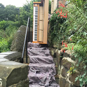 A member of our piano transport team moving a piano up stone steps