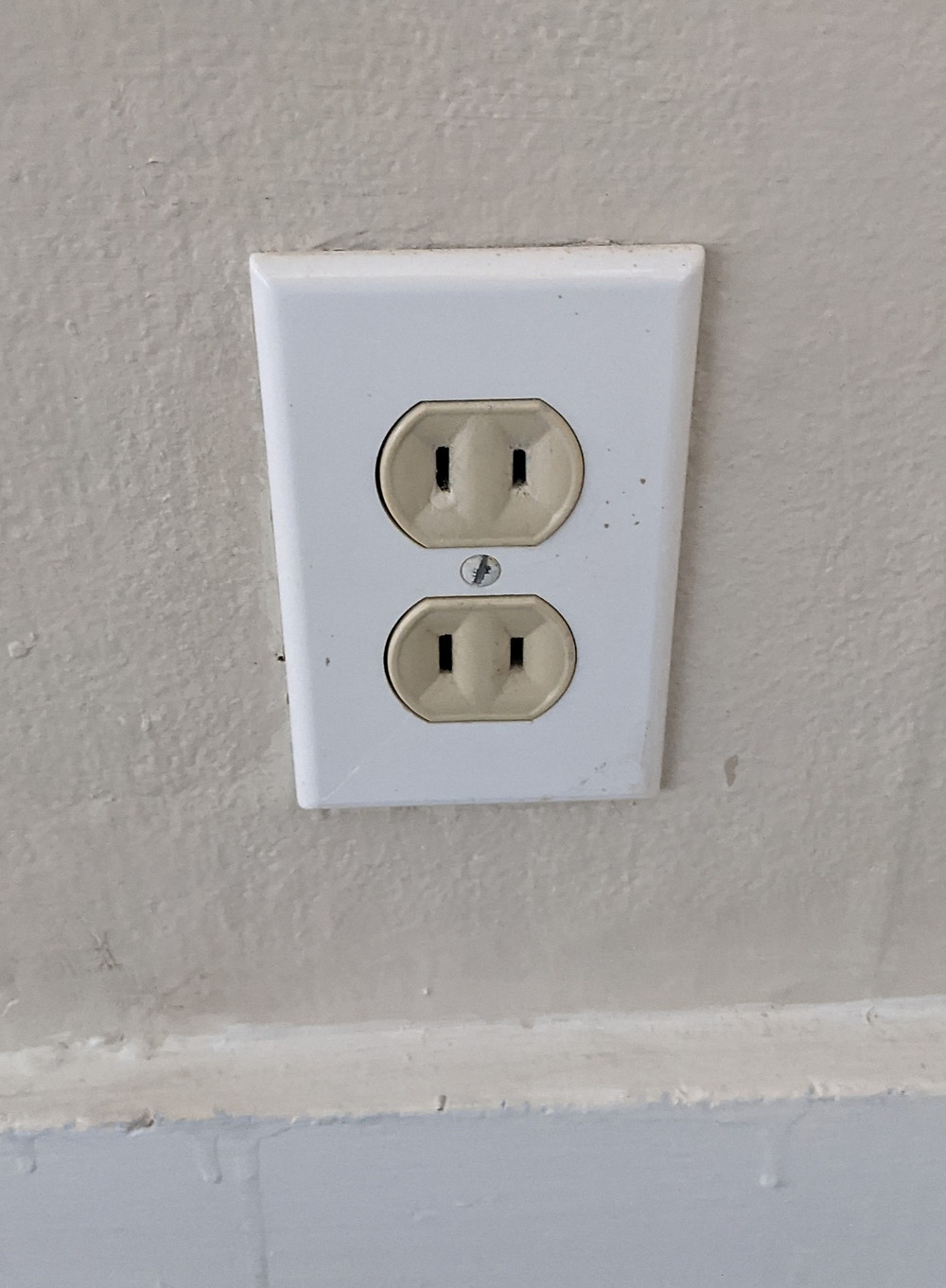 An old, 2 prong outlet. Often people upgrade but don't add a ground