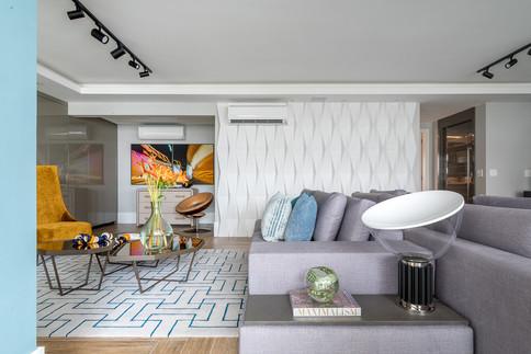 Vista de sala de estar com destaque para revestimento branco em 3D