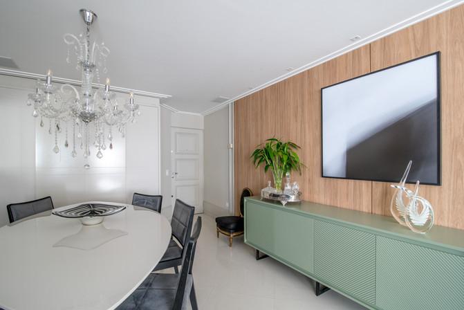 Sala de jantar com mesa oval, buffet verde e painel amadeirado