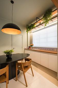Sala de jantar com mesa oval preta e prateleiras iluminadas