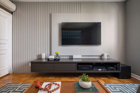 Painel de tv cinza liso e parede com marcenaria ripada