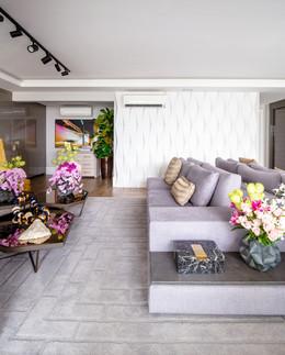 Varanda bem iluminada com sofá e tapete cinzas