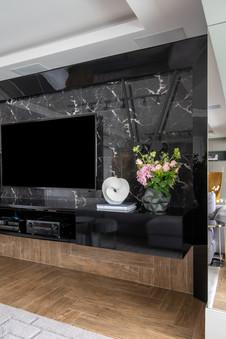 Detalhe de painel marmorizado com rack e moldura em marcenaria preta