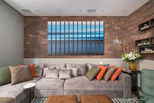 Sala de tv com parede de tijolinhos e composição de quadros