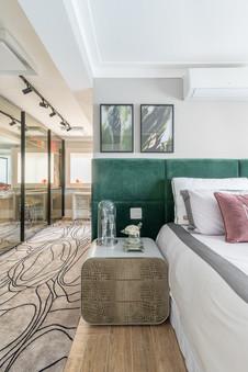 Closet e detalhe de quarto com cabeceira estofada verde