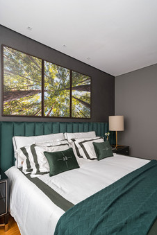 Suite sofisticada com cabeceira e enxoval verde