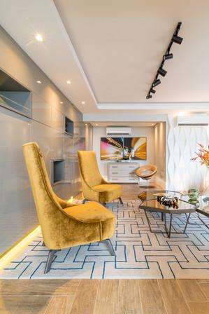 Sala com marcenaria planejada e poltronas em destaque