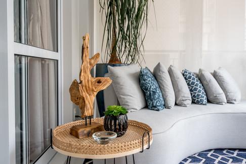 Detalhe mesa lateral em palhinha e sofá curvo