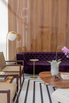Detalhe de varanda com painel de madeira e sofá roxo