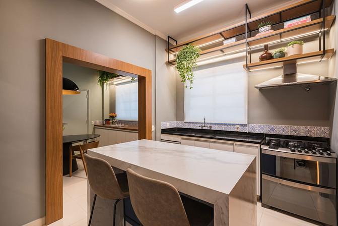 Cozinha com ilha marmorizada - porta com moldura de madeira