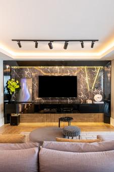 Painel de TV com fundo em porcelanato marmorizado preto e iluminação personalizada