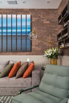 Detalhe sala de tv com parede de tijolinho e composição de quadros