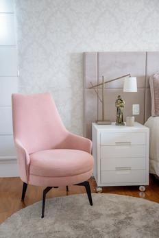 Poltrona rosa, cabeceira estofada e papel de parede romântico