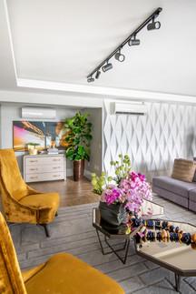 Sala com dupla de poltronas na cor ocre e parede com revestimento branco 3D