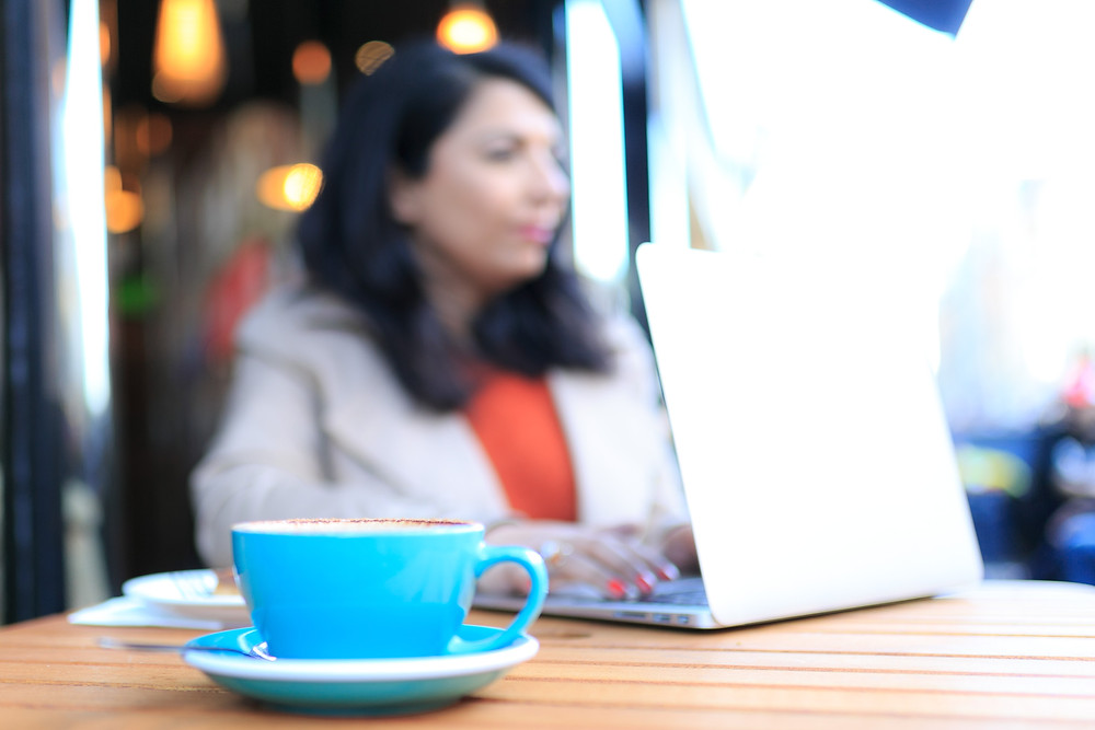 Lady in Leicester with a coffee cup and on laptop outside