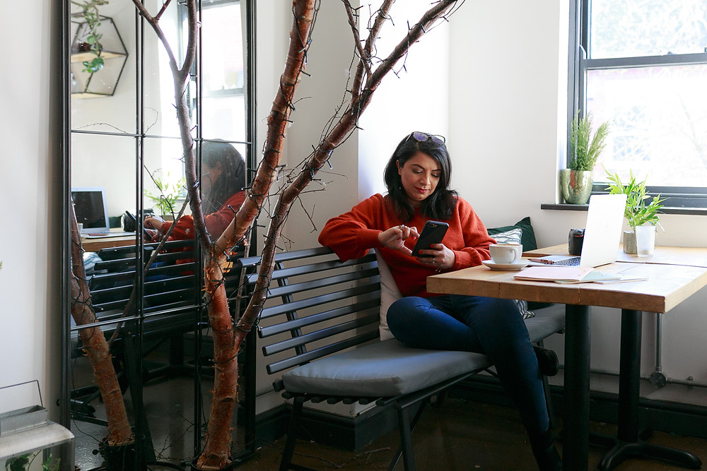 Texting a client during her branding shoot in coffee shop