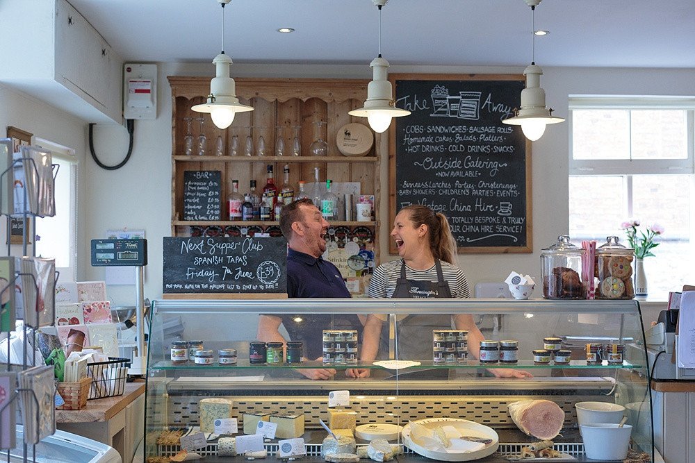man and woman looking at each other and laughing in a deli