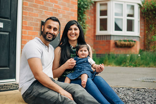 Couple with young child on doorstep in Leicester