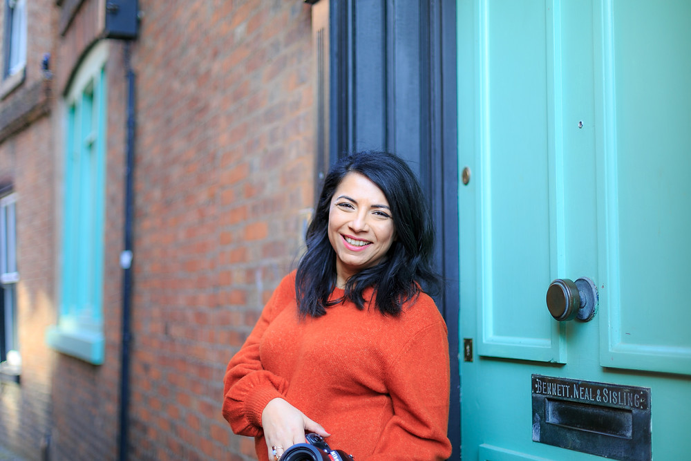Happy photographer during personal branding shoot against green door in Leicester