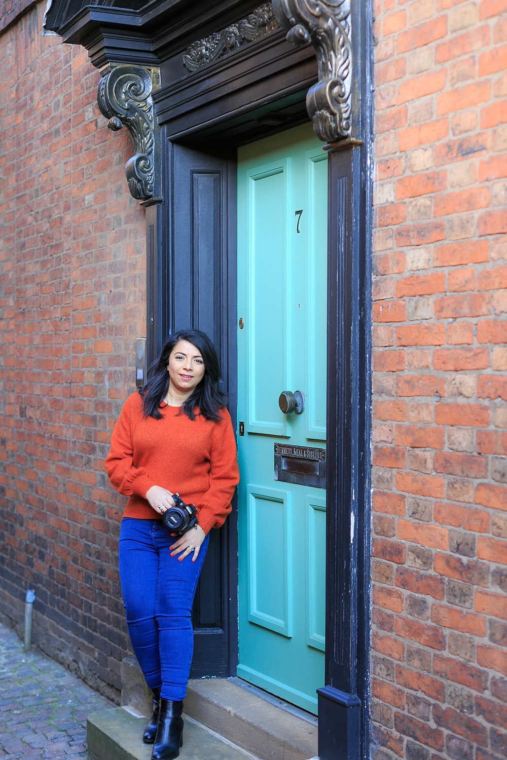 Posing with camera in a green doorway