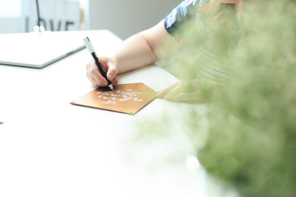 lady writing on a brown board in white pen