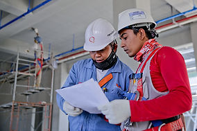 Two construction workers wearing safety gear and reviewing workers compensation insurance policy at a construction site