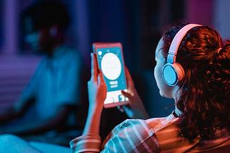 back-view-woman-home-using-headphones-ta