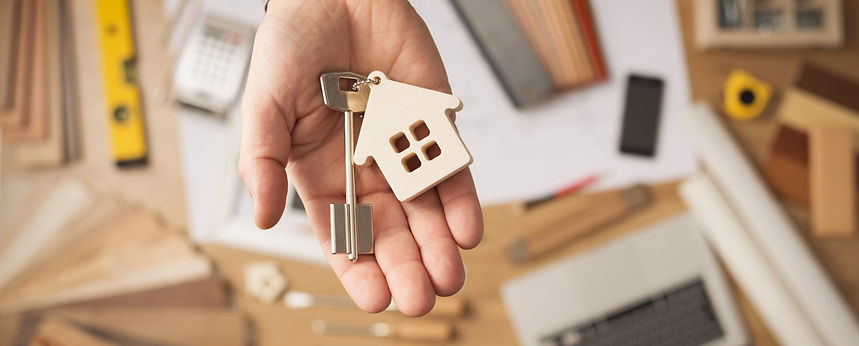 Picture of one hand holding a key and a wooden house cutout.