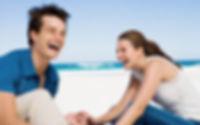 Paare am Strand Lachen