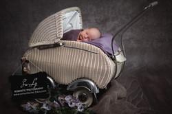 Neugeborenes Baby in altem Kinderwagen.