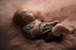 Neugeborenes Baby in Spitzen Strampler
