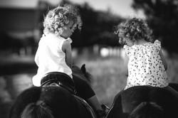 Zwillingskinderfoto auf Pony