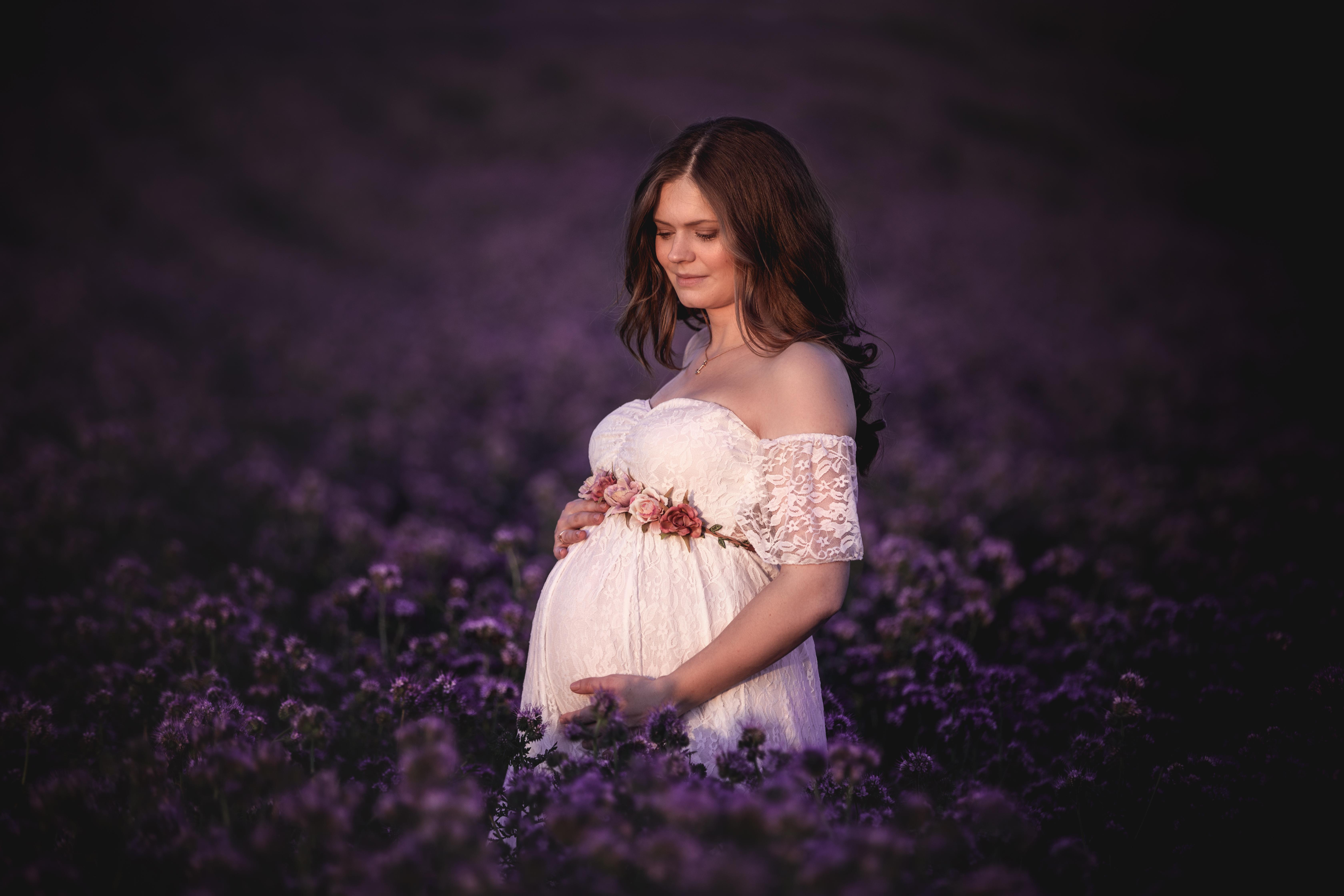 Schwangerschaftsfoto im lila Blumenfeld