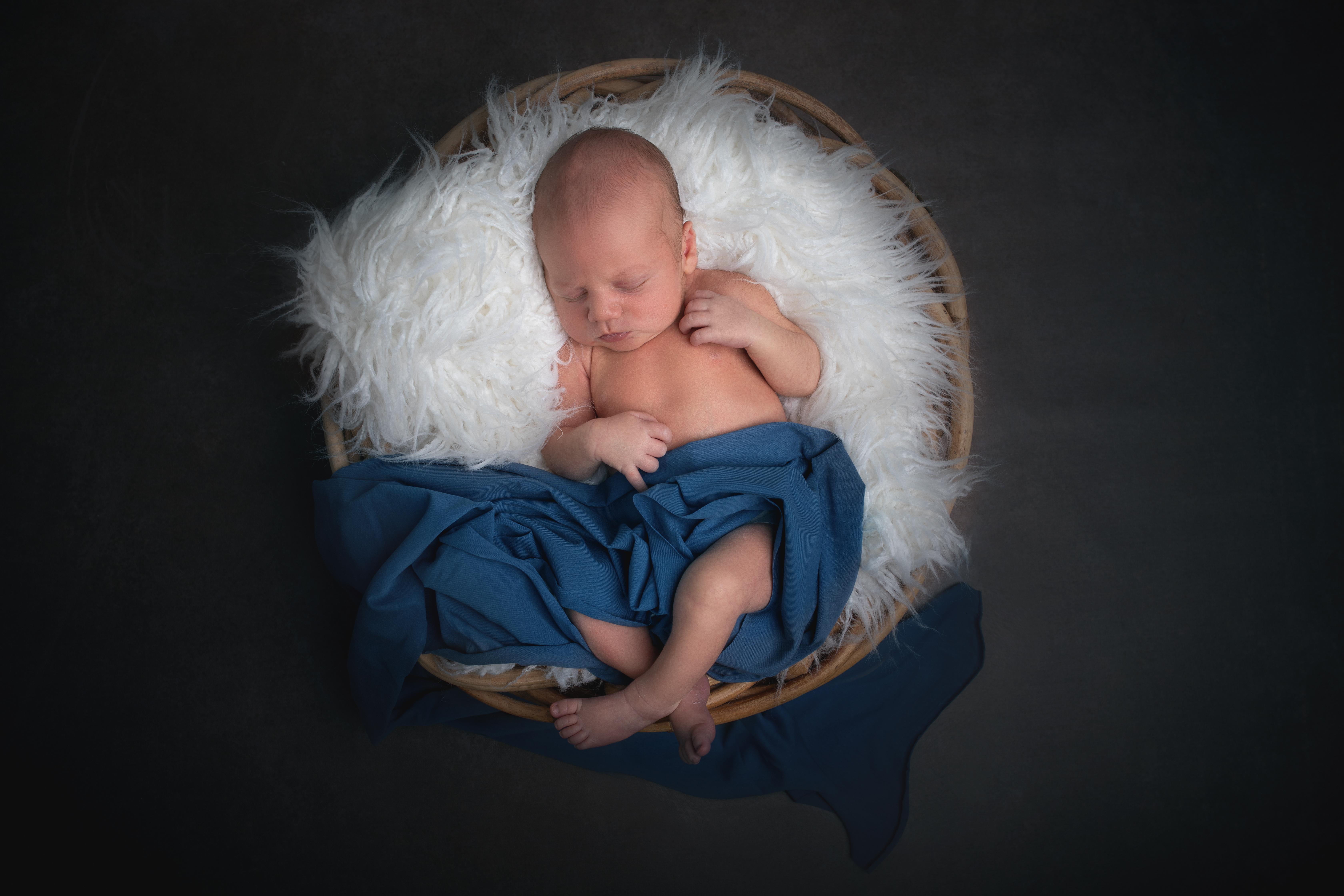Baby mit Flokati  und Rattankorb