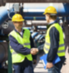 image of two engineers shaking hands at an industrial site