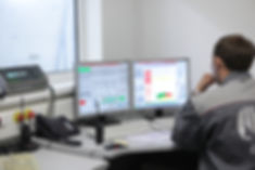 image of man at desk in front of two SCADA screens