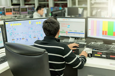 image of a man at a desk monitoring processes shown on a SCADA system